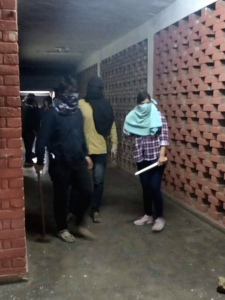 New Delhi: Students roam around the JNU hostel with rods and sticks after clashes erupted between groups of students at JNU campus in New Delhi on Jan 5, 2020. (Photo: IANS)
