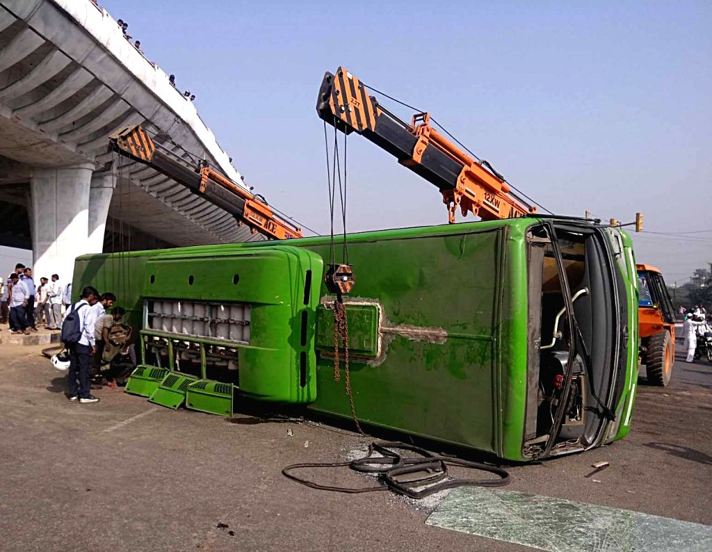:New Delhi: The Delhi Transport Corporation (DTC) bus that overturned following a collision with a dumper truck injuring around 10 people on Wazirabad flyover, in New Delhi on Oct 17, 2018. (Photo: ...