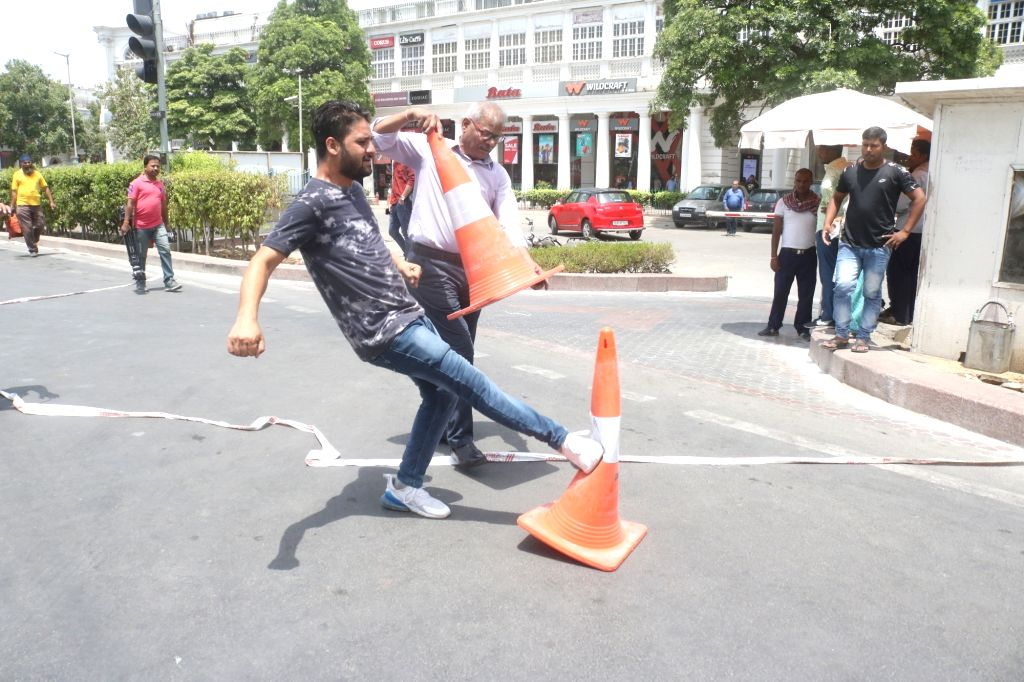 New Delhi: Traders remove traffic cones during a protest against NDMC for restricting vehicular movement in the inner circle of Connaught Place in New Delhi on June 29, 2019. (Photo: Bidesh Manna/IANS)