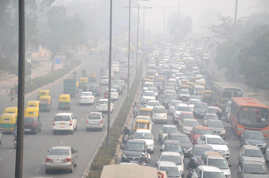 Traffic slows down on Vikas Marg due to dense fog cover in New Delhi, on Dec 22, 2014.