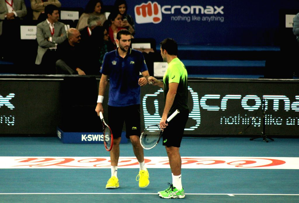 UAE Royals Marin Cilic and Nenad Zimonjic in action during their doubles match against Singapore Slammers Lleyton Hewitt and Nick Kyrgios on the Coca-Cola International Premier Tennis ...