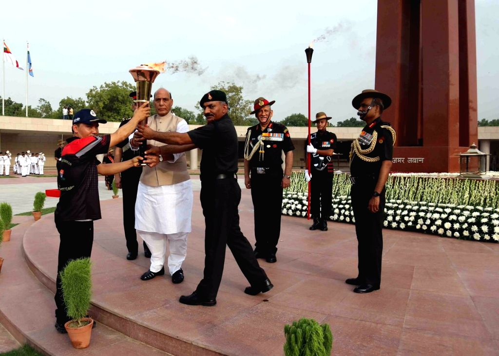 New Delhi: Union Defence Minister Rajnath Singh hands over the 'Victory Flame' to Indian Army at National War Memorial in New Delhi, which would travel through towns and cities to finally culminate at Dras in Jammu and Kashmir's - Rajnath Singh