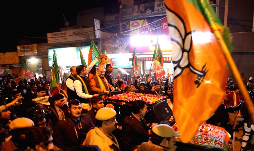 New Delhi: Union Home Minister Amit Shah along with BJP MP Parvesh Verma and the party's electoral candidate Krishn Gahlot, holds a roadshow ahead of the February 8 Delhi Assembly elections, on Jan 23, 2020. (Photo: IANS) - Amit Shah and Parvesh Verma