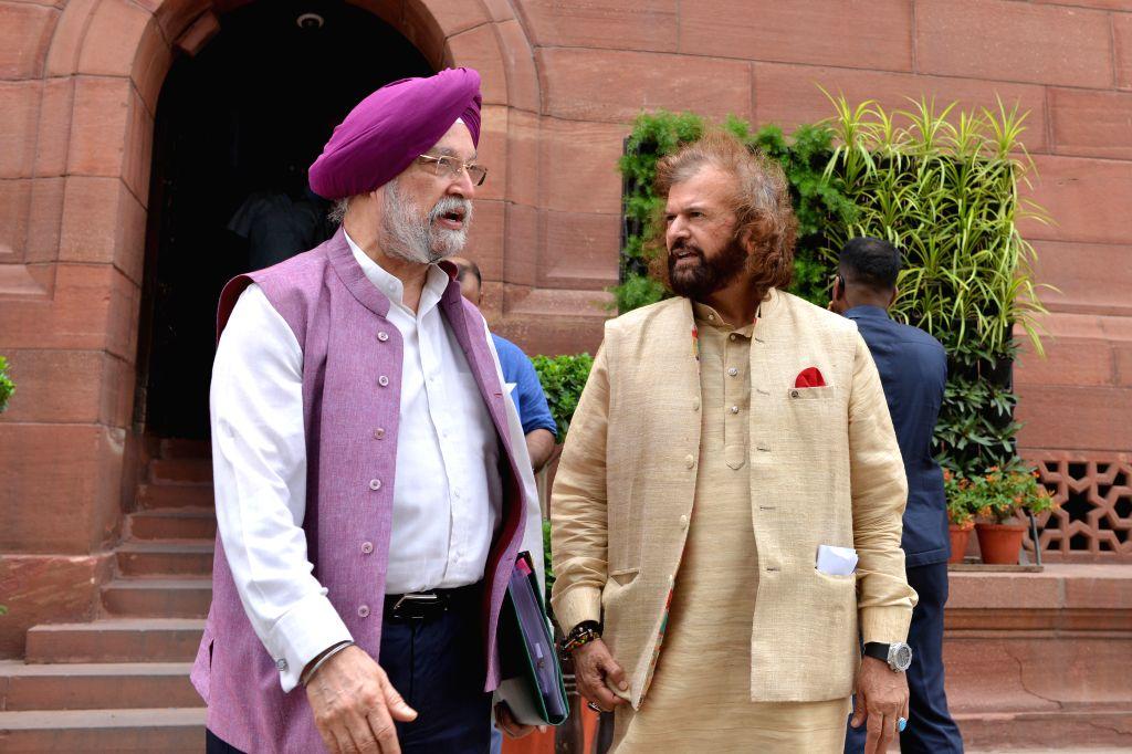 New Delhi: Union MinisterHardeep Singh Puri in a conversation with BJP MPHans Raj Hans at Parliament, in New Delhi on July 11, 2019. (Photo: IANS) - Hardeep Singh Puri