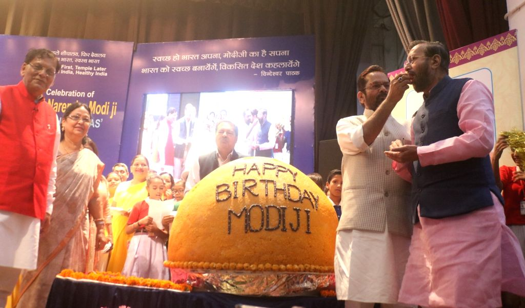 :New Delhi: Union ministers Prakash Javdekar, Mukhtar Abbas Naqvi with Sulabh International founder Bindeshwar Pathak unveiled a 568 Kg laddu as part of celebration of Prime Minister Narendra ...