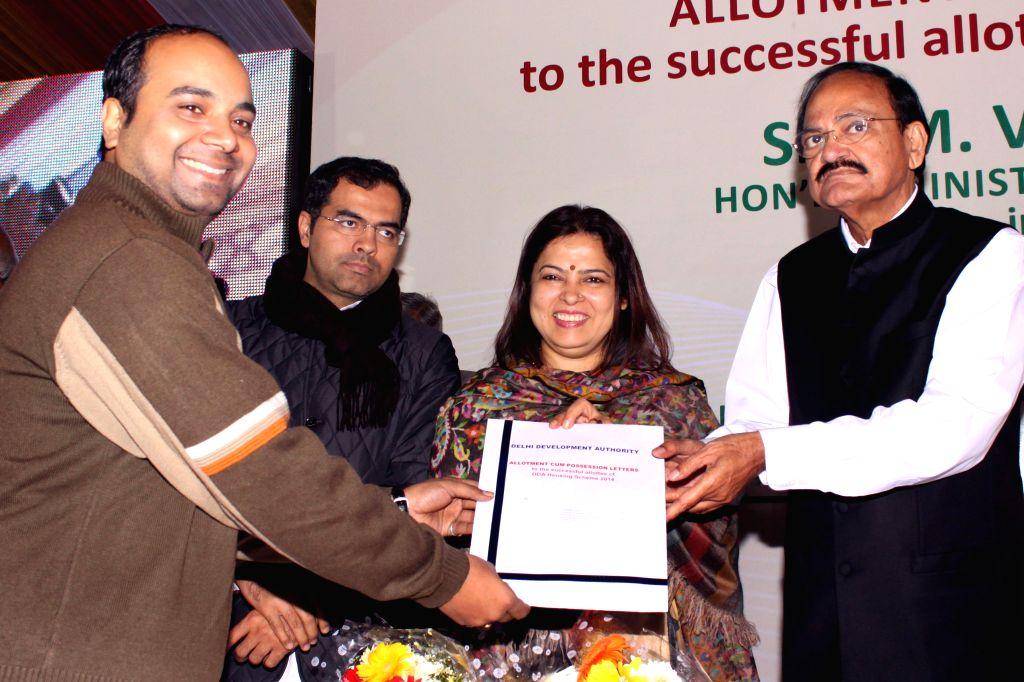 Urban Development Minister M Venkaiah Naidu presenting the allotment cum possession letter to successful allottees of DDA housing scheme 2014, in New Delhi on Jan. 03, 2015. - M Venkaiah Naidu