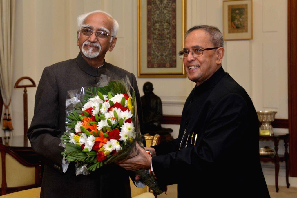 Vice-President Mohammad Hamid Ansari calls on President Pranab Mukherjee to wish him on new year at Rashtrapati Bhavan in New Delhi, on Jan 1, 2015. - Pranab Mukherjee
