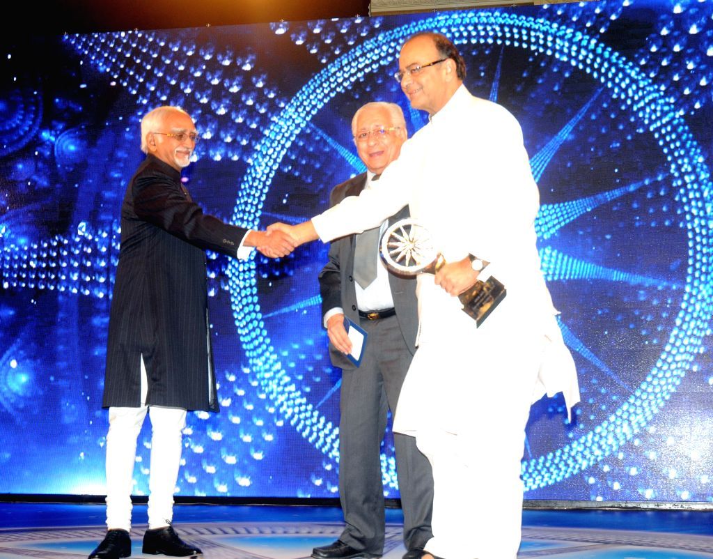 Vice President Mohd. Hamid Ansari presents the CNN-IBN Indian of the Year Award 2014 to the Union Minister for Finance, Corporate Affairs and Information and Broadcasting Arun Jaitley, in ...