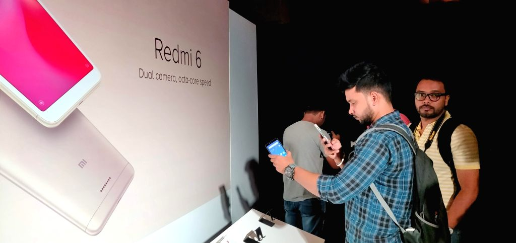 New Delhi: Visitors check out the features of newly launched Xiaomi Redmi 6 series smartphone, in New Delhi, on Sept 5, 2018. Also launched Xiaomi Redmi 6A and Redmi 6 Pro smartphone. (Photo: IANS)