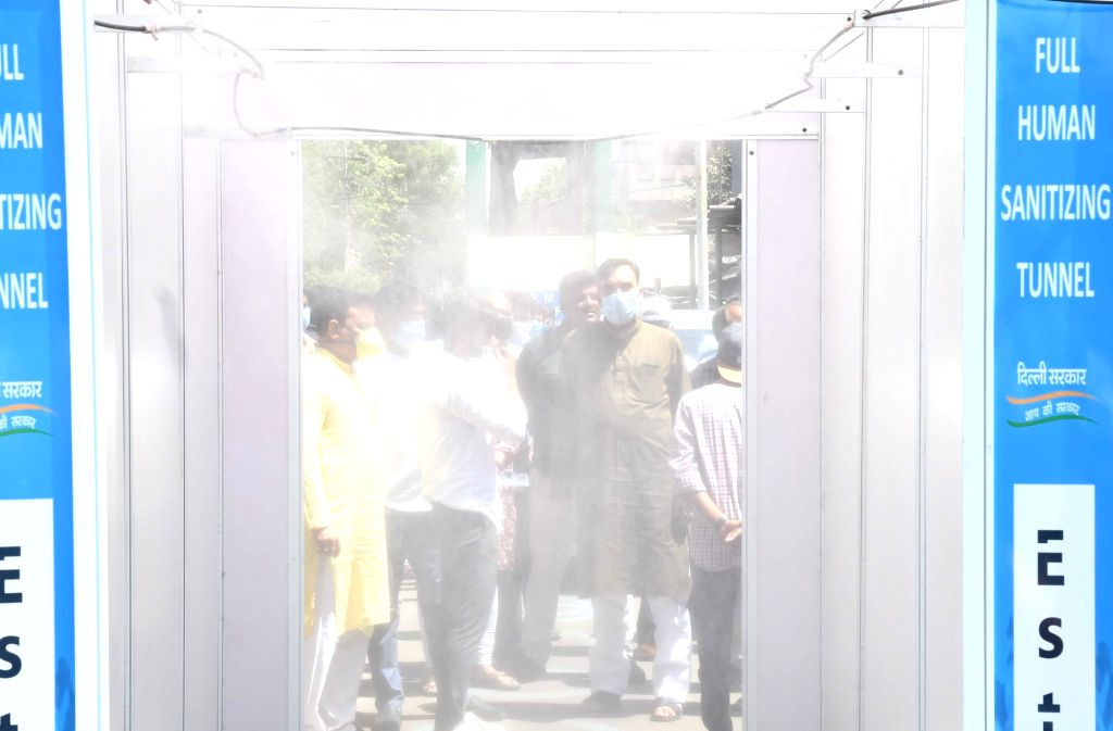 New Delhi: Visitors disinfect themselves using a sanitisation tunnel installed at Delhi's Azadpur Subzi Mandi during the 21-day nationwide lockdown (that entered the 17th day) imposed as a precautionary measure to contain the spread of coronavirus, o