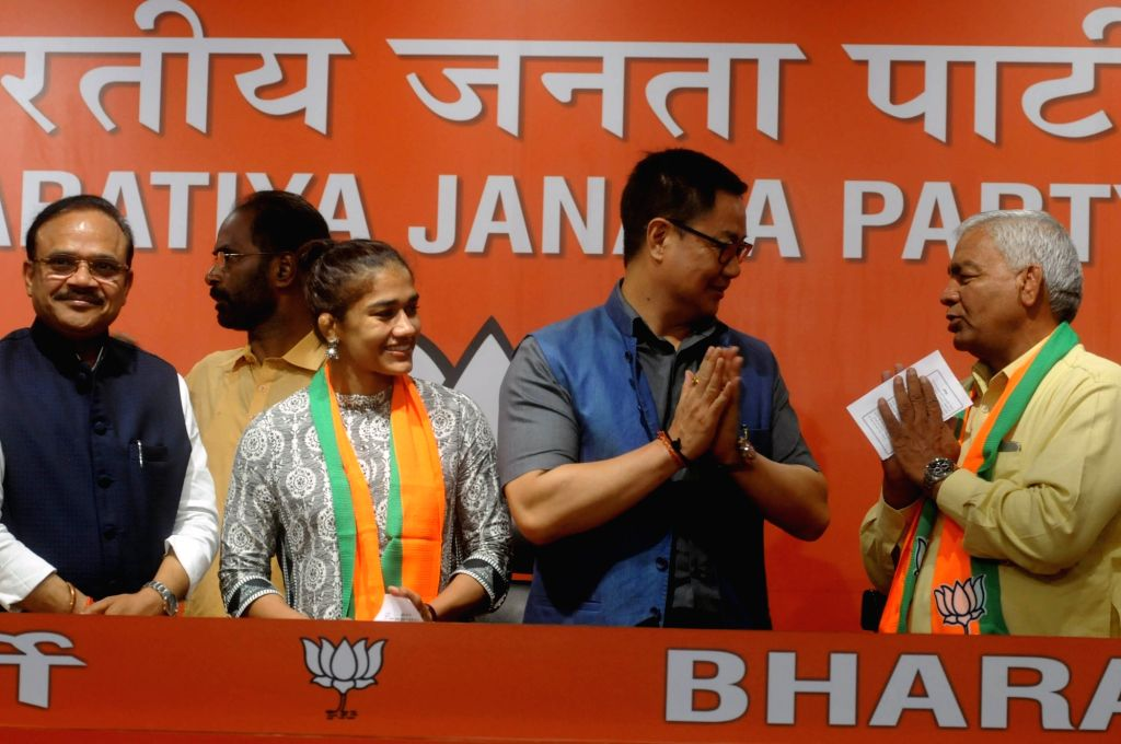 New Delhi: Wrestler and Commonwealth Gold Medalist Babita Phogat and her father Mahavir Singh Phogat join BJP in the presence of Union Sports and Youth Affairs Minister and BJP leader Kiren Rijiju and party's general secretary in-charge of Haryana An - Mahavir Singh Phogat and Haryana Anil Jain