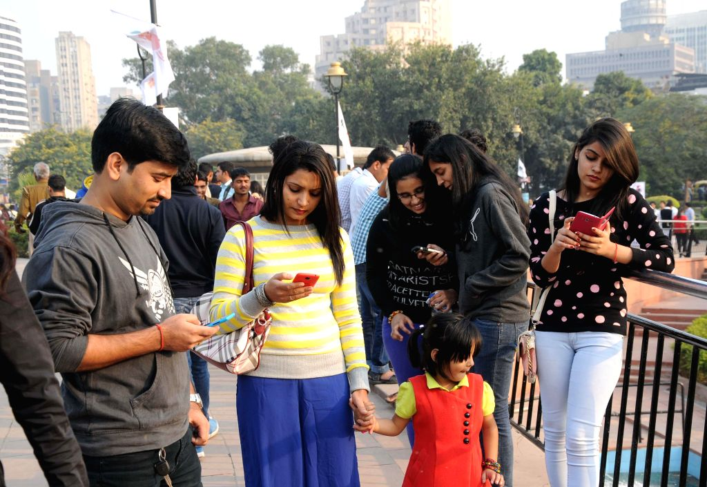 Youth checkout wi-fi connectivity at the Central Park of Connaught Place in New Delhi, on Nov 16, 2014. The Wi-Fi services were launched by New Delhi MP Meenakshi Lekhi.
