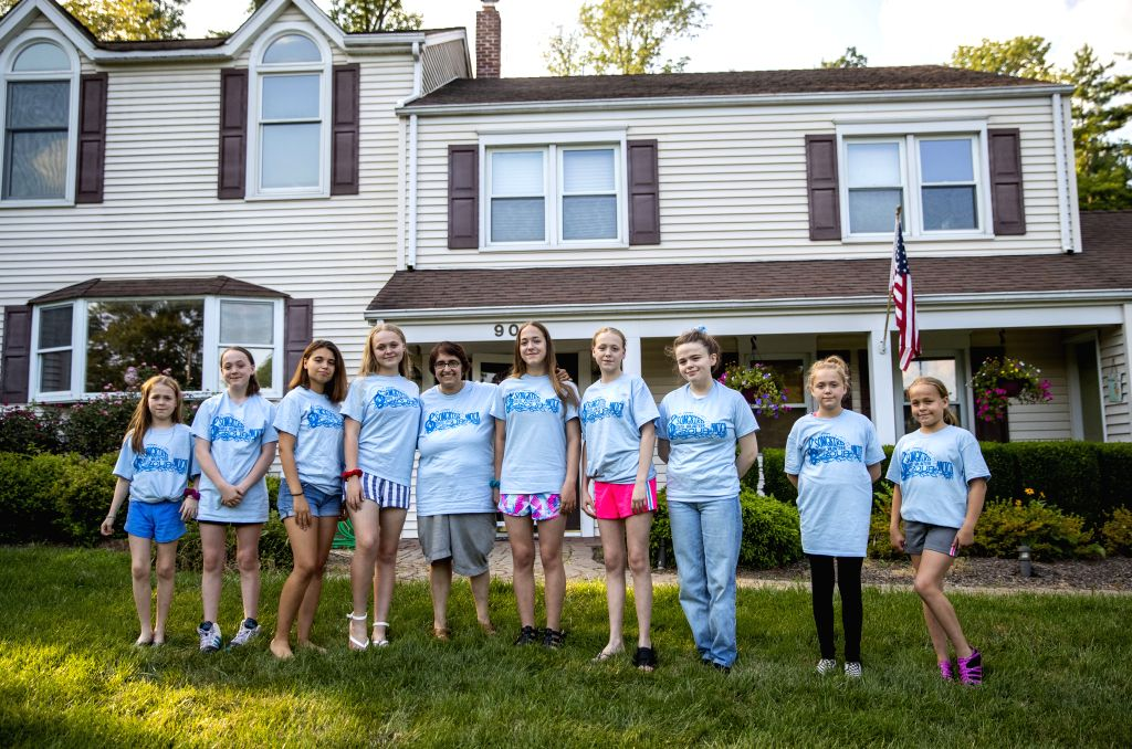 NEW JERSEY, Aug. 10, 2019 - Lynn Berat (5th L) and her nine daughters pose for a photo in front of their Chinese teacher's house in Bernards of New Jersey, the United States, July 27, 2019. Lynn ...