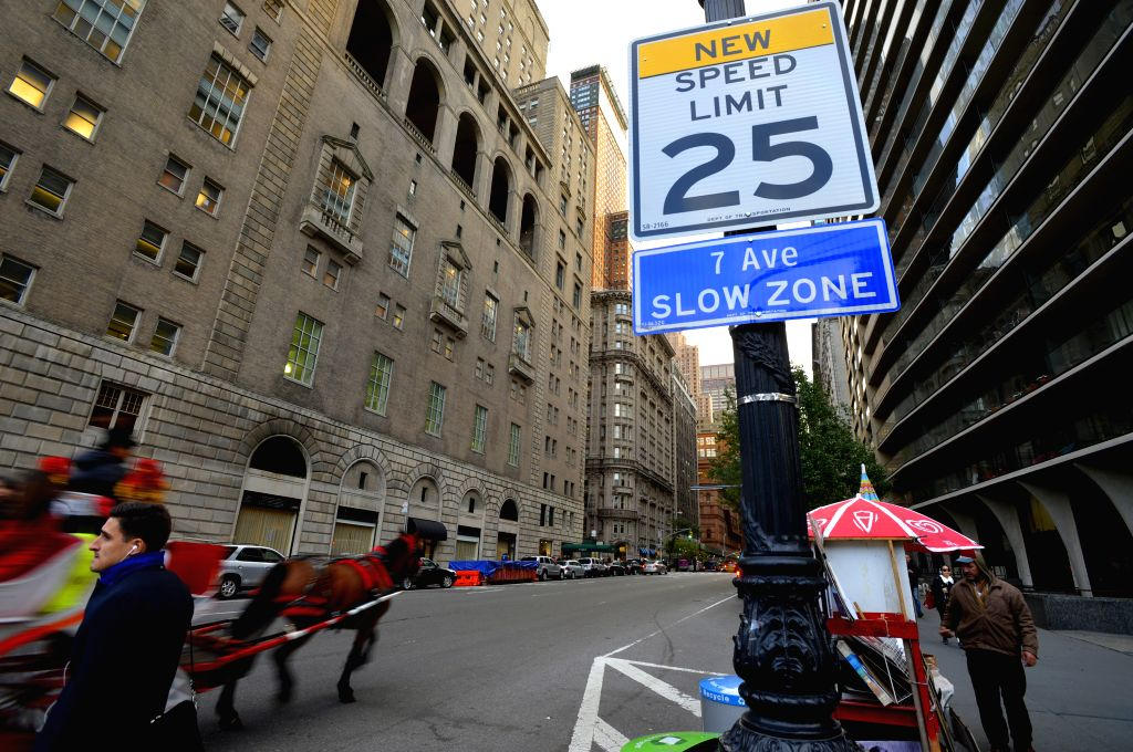 New York: A carriage passes by a traffic sign of new speed limit on the 7th Avenue in Manhattan, New York, the United States, Nov. 7, 2014. A new speed limit of 25 miles an hour, reduced from the ...