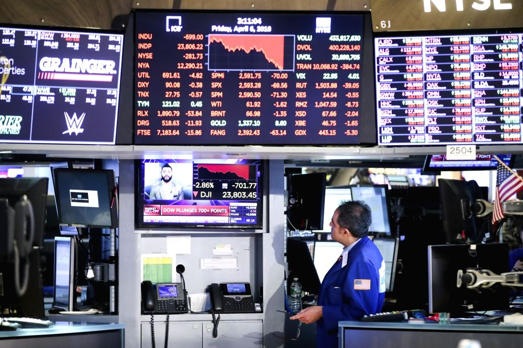 NEW YORK, April 6, 2018 - A trader watches a news report at the New York Stock Exchange in New York, the United States, on April 6, 2018. The Dow Jones Industrial Average erased 572.46 points, or ...