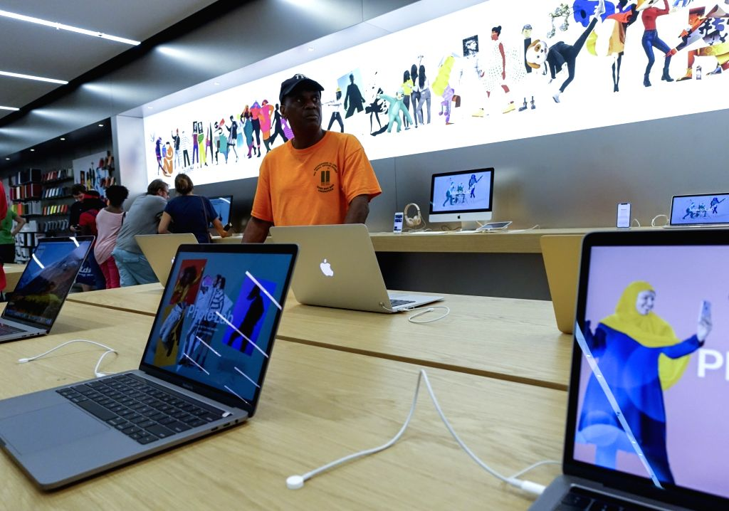 NEW YORK, Aug. 2, 2018 - Customers select products at an Apple store in New York, the United States, Aug. 2, 2018. U.S. tech giant Apple became the first American company that saw its market cap hit ...