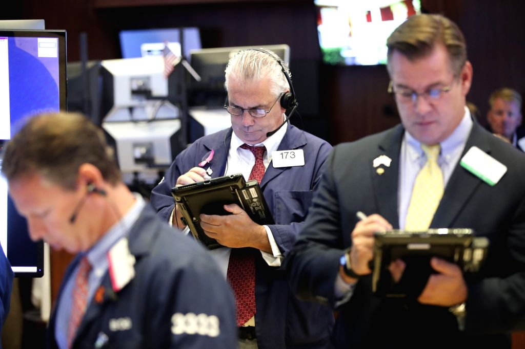 NEW YORK, Aug. 6, 2018 - Traders work at the New York Stock Exchange in New York, the United States, Aug. 6, 2018. U.S. stocks closed higher on Monday as investors digested a batch of second-quarter ...