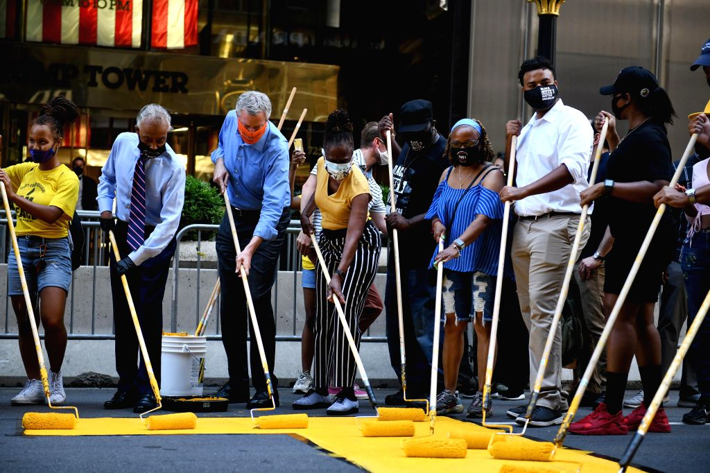 """New York City Mayor Bill de Blasio (3rd L) helps to paint """"Black Lives Matter"""" mural in front of Trump Tower in New York, the United States, on July 9, ..."""