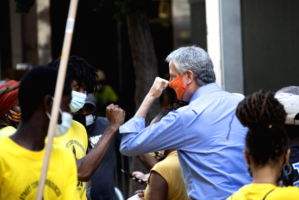 """New York City Mayor Bill de Blasio (C-R) greets a participant after he helped to paint """"Black Lives Matter"""" mural in front of Trump Tower in New York, the ..."""