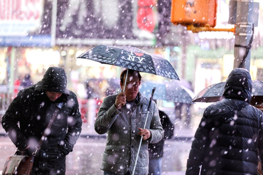 NEW YORK, Dec. 3, 2019 - Pedestrians walk at Times Square in New York, the United States, Dec. 2, 2019. Heavy rain and snow hit the city on Monday.