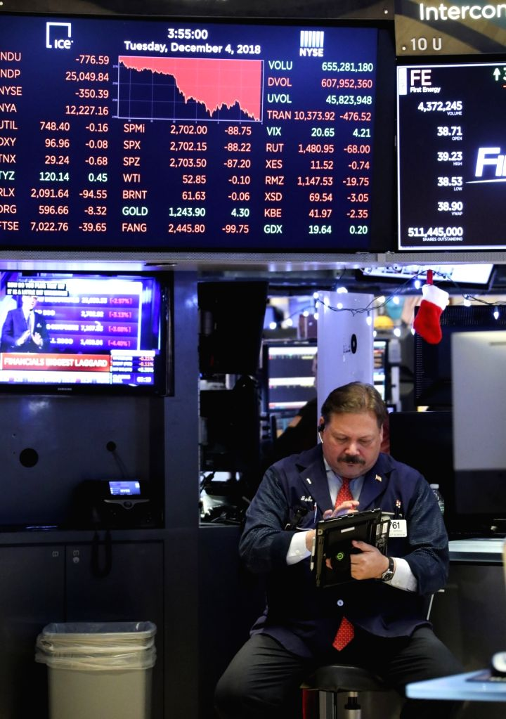 NEW YORK, Dec. 5, 2018 - A trader works at the New York Stock Exchange in New York, the United States, Dec. 4, 2018. U.S. stocks plunged on Tuesday, with all three major indices erasing more than 3 ...