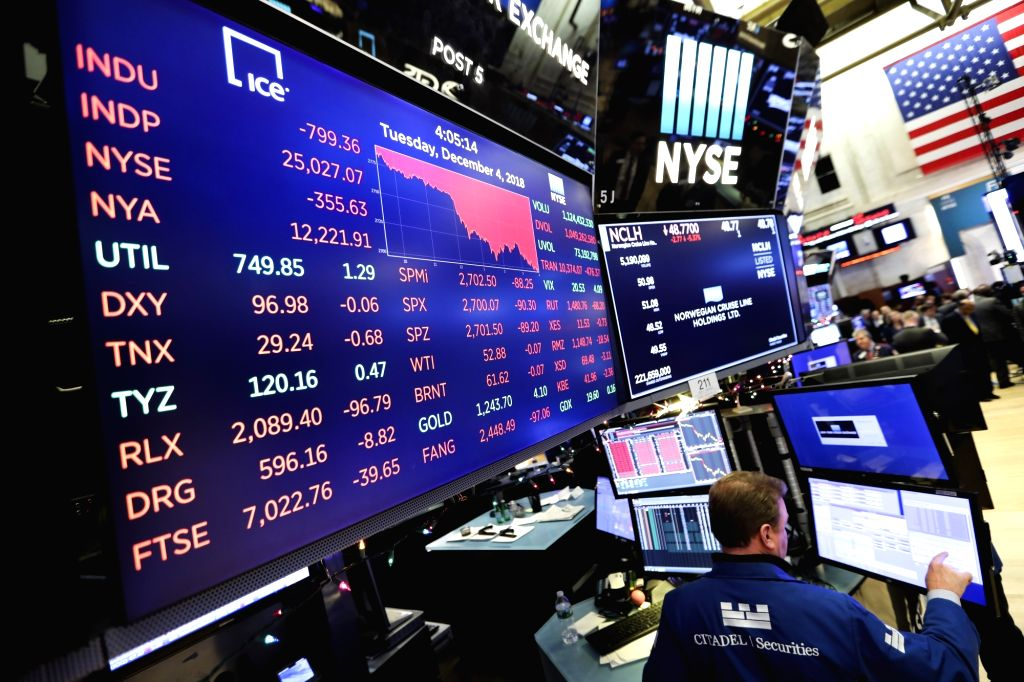 NEW YORK, Dec. 5, 2018 - Traders work at the New York Stock Exchange in New York, the United States, Dec. 4, 2018. U.S. stocks plunged on Tuesday, with all three major indices erasing more than 3 ...