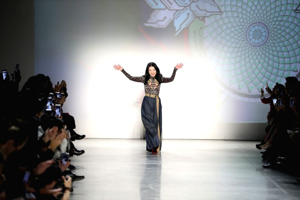 NEW YORK, Feb. 14, 2018 - Designer Vivienne Tam gestures after models preseting her creations during the New York Fashion Week in New York, the United States, Feb. 13, 2018.