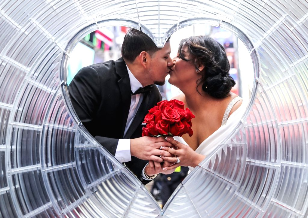 """NEW YORK, Feb. 14, 2018 - Kelly Zapata and Anthonny Espejo pose for photos before the """"Weddings in the Square"""" Valentine's Day event at Times Square in New York, the United States, on Feb. ..."""