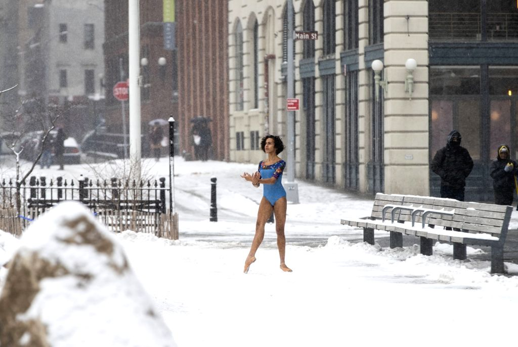 NEW YORK, Feb. 20, 2019 - A girl poses for photos in the snow near the Brooklyn Bridge in New York, the United States, Feb. 20, 2019. More than 1,000 flights were canceled in airports across the ...