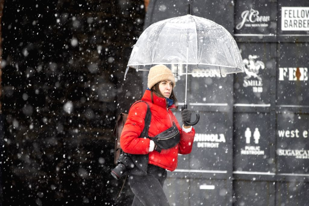 NEW YORK, Feb. 20, 2019 - A woman walks in the snow near the Brooklyn Bridge in New York, the United States, Feb. 20, 2019. More than 1,000 flights were canceled in airports across the United States ...