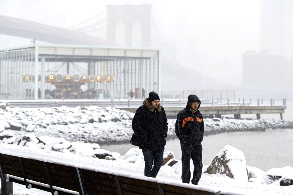 NEW YORK, Feb. 20, 2019 - People walk in the snow near the Brooklyn Bridge in New York, the United States, Feb. 20, 2019. More than 1,000 flights were canceled in airports across the United States ...