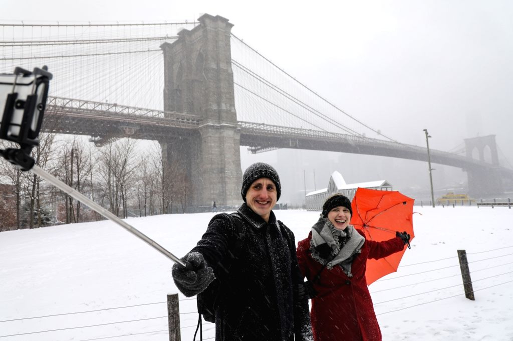 NEW YORK, Feb. 20, 2019 - Tourists take a selfie in the snow near the Brooklyn Bridge in New York, the United States, Feb. 20, 2019. More than 1,000 flights were canceled in airports across the ...