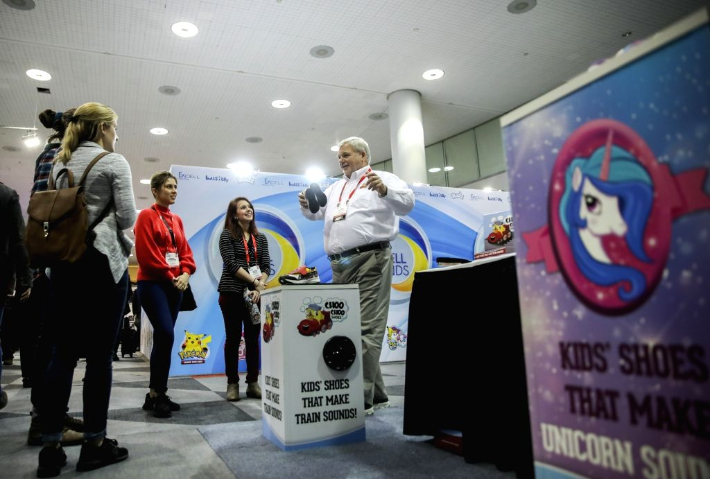 NEW YORK, Feb. 25, 2019 - Ken Silvestri (1st R), a staff worker of Choo Choo Shoes, shows the company's products to visitors at their booth during the 116th Annual North American International Toy ...