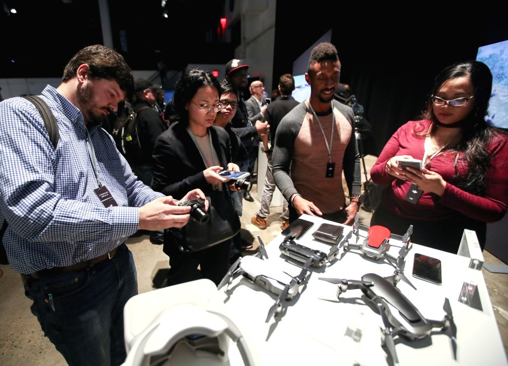 NEW YORK, Jan. 23, 2018 - Guests and journalists take photos of Mavic Air and its accessories during a launching ceremony in New York, the United States, Jan. 23, 2018. Civilian drones producer DJI ...
