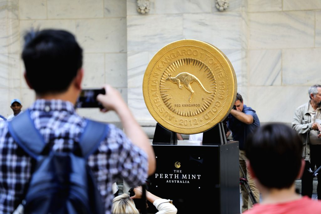 NEW YORK, July 16, 2019 - A man takes photos of a gold coin in front of the New York Stock Exchange in New York, the United States, July 16, 2019. The colossal one tonne gold coin was displayed here ...