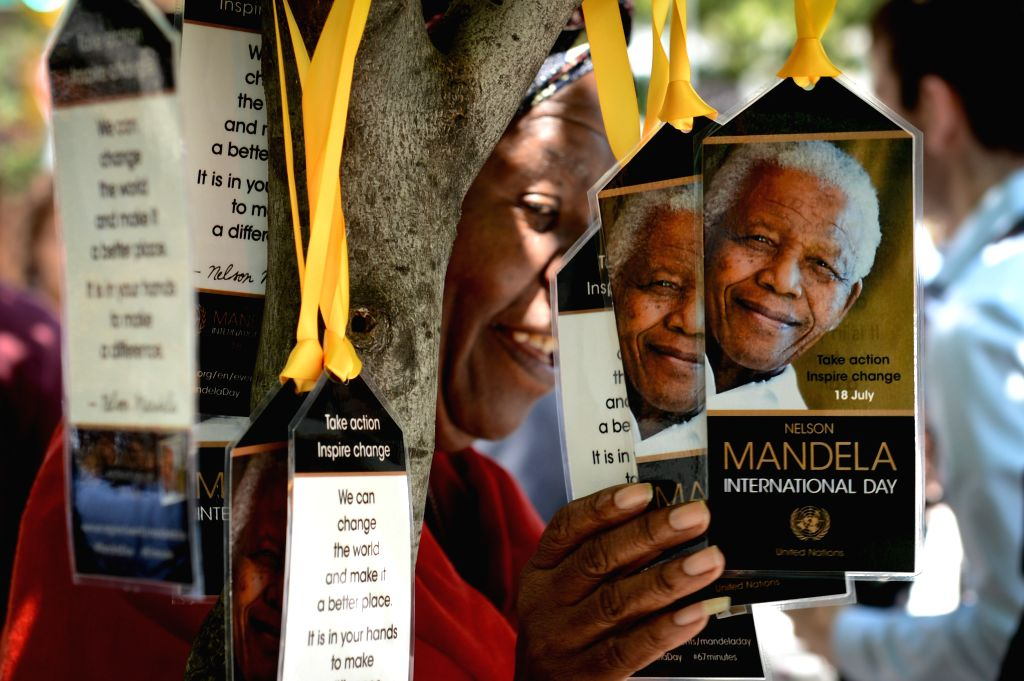 A woman poses for a picture with tags featuring Mandela's portrait during a ceremony commemorating Nelson Mandela International Day, in front of the UN ...