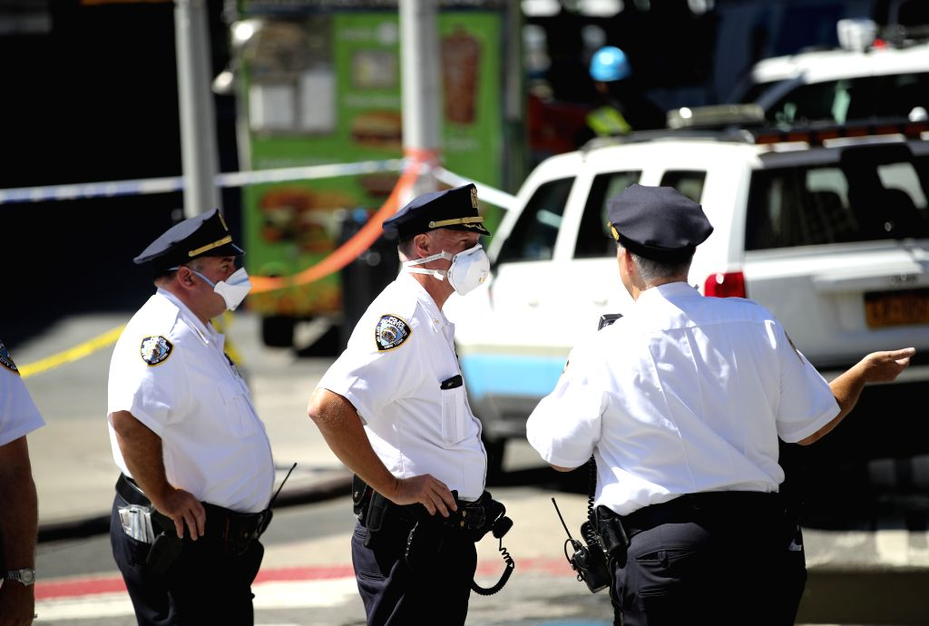 NEW YORK, July 19, 2018 - Police officers are seen with masks as they stand guard near the spot of a steam pipe explosion in New York, the United States, July 19, 2018. A neighborhood in Manhattan, ...