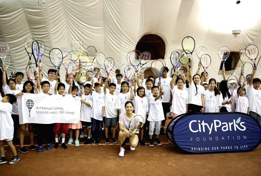 NEW YORK, July 19, 2019 - Two-time Grand Slam Champion Chinese tennis player Li Na (front) poses with young tennis players during a youth tennis clinic in Mahattan of New York, the United States, ...