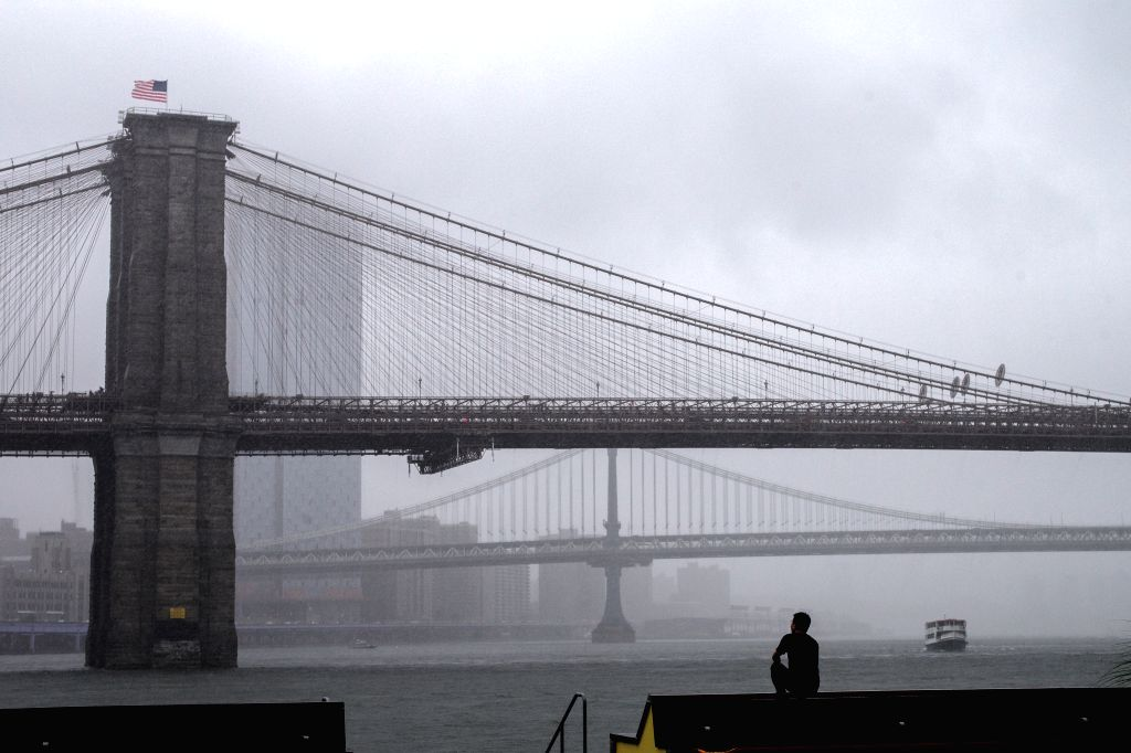 NEW YORK, July 23, 2018 - A man is pictured sitting in the pouring rain in Manhattan of New York City, the United States, July 22, 2018.