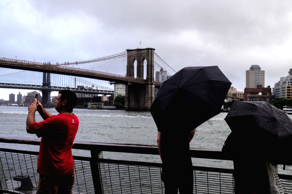 NEW YORK, July 23, 2018 - A man takes pictures of the Brooklyn Bridge in Manhattan of New York City, the United States, July 22, 2018.