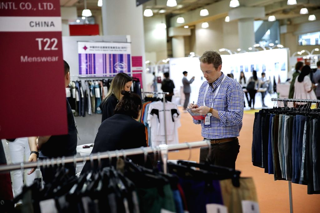 NEW YORK, July 24, 2018 - An American buyer takes notes at the booth of a Chinese clothing producer at the Chinese Textile and Apparel Trade Show in New York, the United States, July 23, 2018. The ...