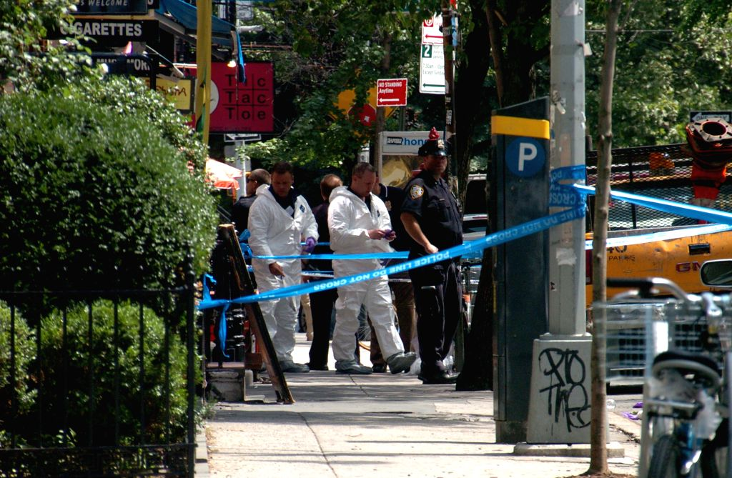 Policemen inspect the site of a shooting in the West Village in Manhattan, New York, the United States, on July 28, 2014. Two deputy U.S. marshals and a NYPD ...