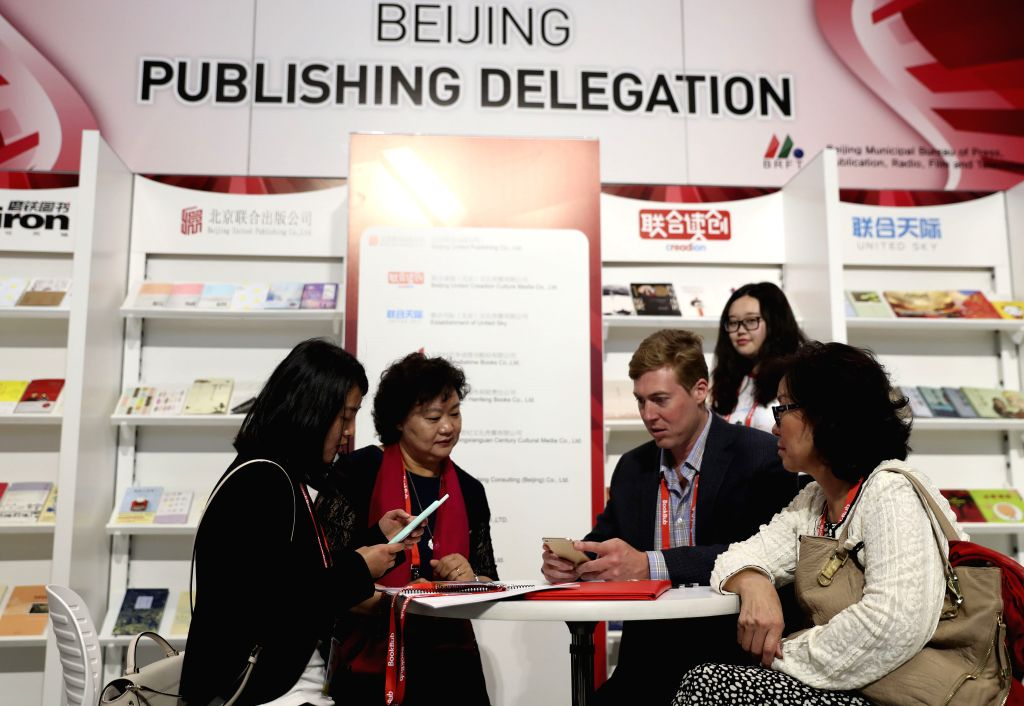 NEW YORK, June 2, 2017 - A publisher (2nd R, Front) talks with staff members at the booth of China's Beijing Publishing Delegation during the BookExpo 2017 in New York, the United States, on June 2, ...