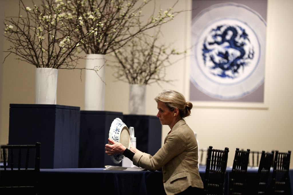 """New York, March 10, 2017 - A visitor looks at a fine blue and white barbed rim """"floral scroll"""" dish during Sotheby's Asia Week exhibition in New York, the United States, on March 10, 2017. ..."""