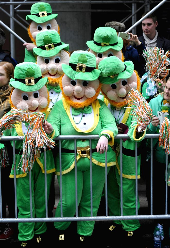 Spectators in green cartoon costumes are seen during the St. Patrick's Day Parade in New York, the United States, March 17, 2015.