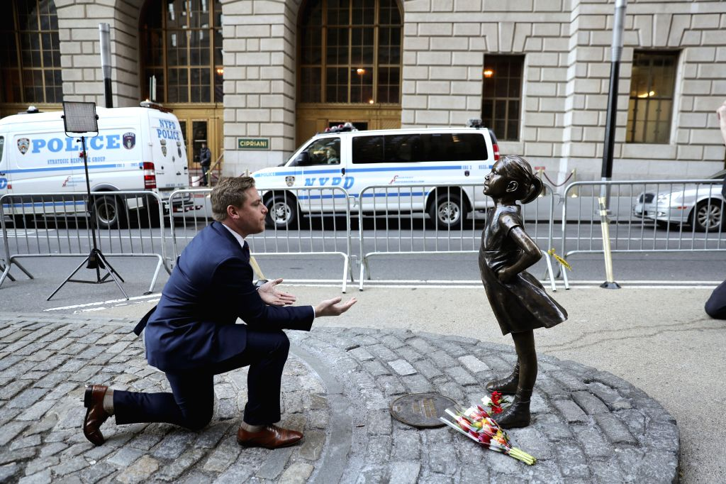 "NEW YORK, March 9, 2017 - A man poses for a photo beside the ""fearless girl"" statue facing the bronze bull statue near the Wall Street in New York, the United States, March 9, 2017. The ..."