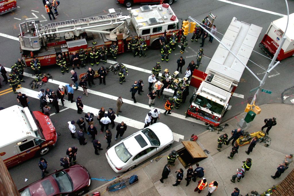 Rescue personnel are busy working above-ground near the site of derailment in the New York City borough of Queens, May 2, 2014. An F train carrying some 1,000 ...
