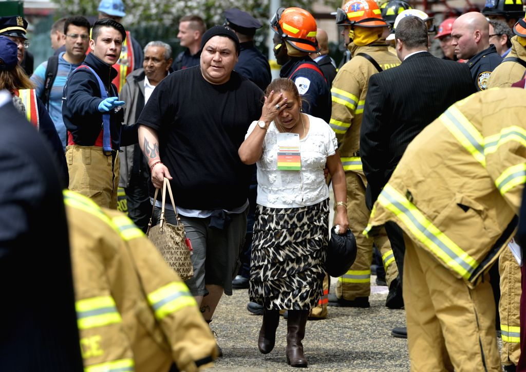 Two passengers walk out of an emergency exit after being evacuated from a derailed train in the New York City borough of Queens, May 2, 2014. An F train carrying ...