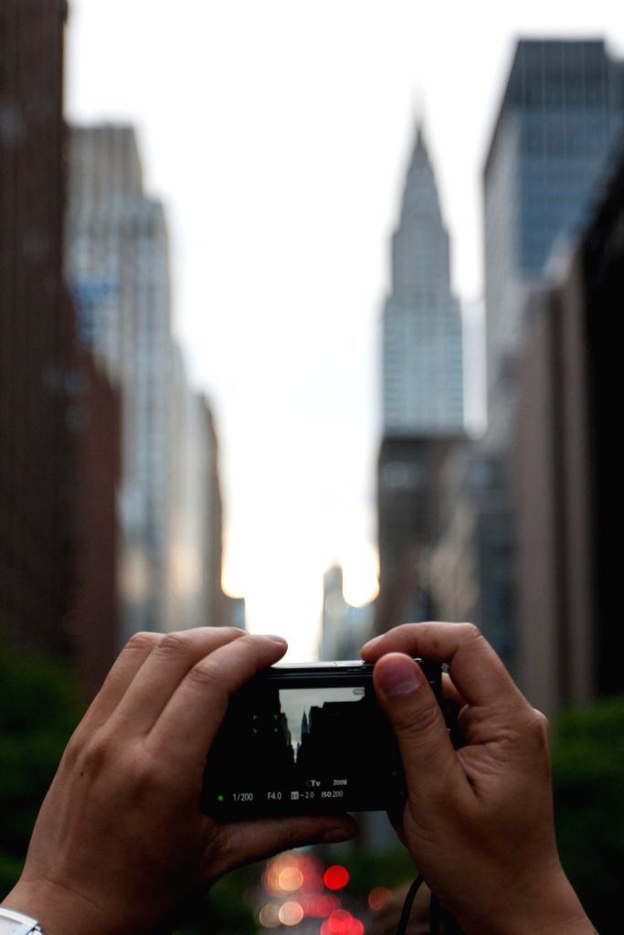 NEW YORK, May 29, 2016 - A man waits to take photos of Manhattanhenge in Manhattan, New York, the United States, on May 29, 2016. Tourists, residents and commuters waited to take photos of the effect ...