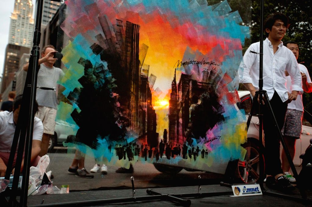 """NEW YORK, May 29, 2016 - Japanese painter Takeshi Sato (R) stands beside his work """"Manhattanhenge 2016"""" in New York, the United States, May 29, 2016. Tourists, residents and commuters ..."""